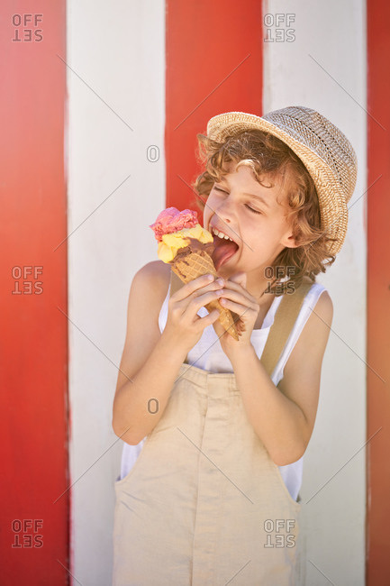 Cheerful boy in beige overalls and straw hat licking ice cream cone while standing against wall with white and red stripes