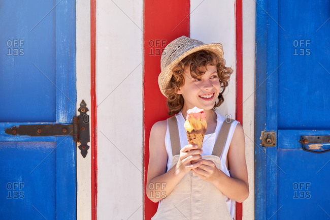 Cheerful boy in beige overalls and straw hat with ice cream cone while standing against wall with white and red stripes