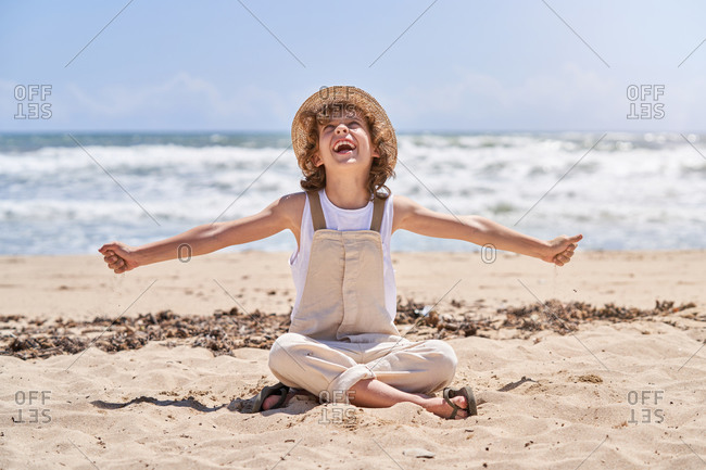 Full body of happy little boy with open arms while sitting with legs crossed on sandy beach near waving sea