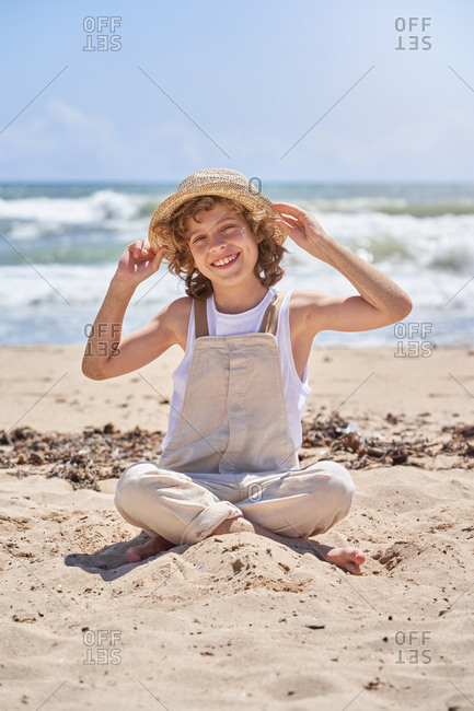 Full body of happy little boy sitting with legs crossed on sandy beach near waving sea