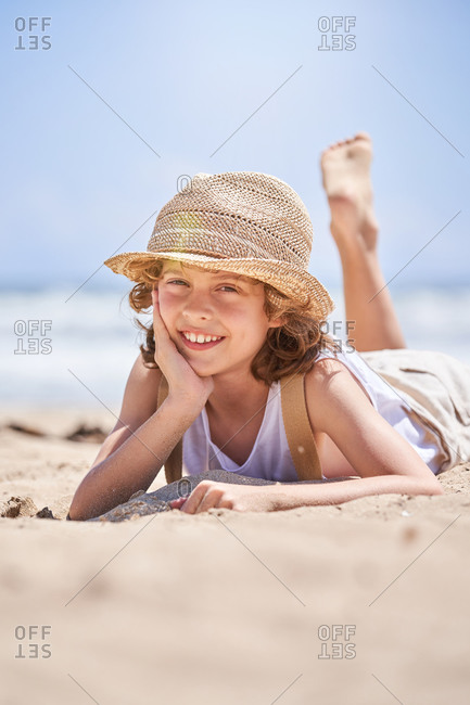 Ground level of full body of cute little boy propping chin while chilling on sandy coast during vacation