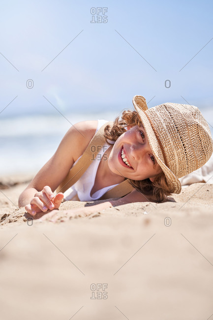 Ground level of full body of cute little boy while chilling on sandy coast during vacation