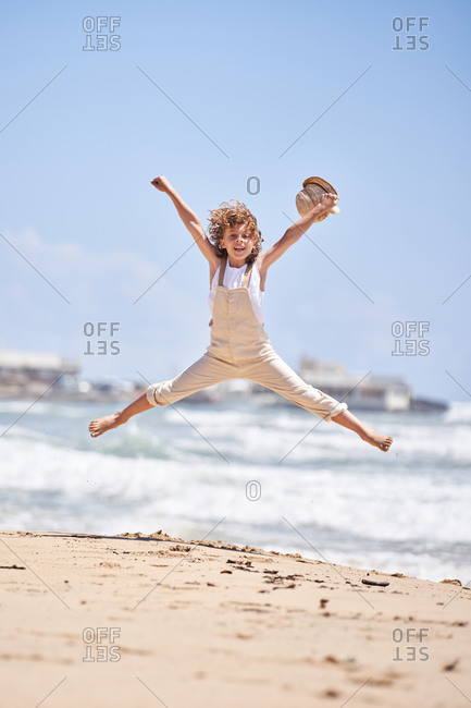 Full body of excited boy with hat in hand having fun on sandy seashore and jumping high while enjoying summer day