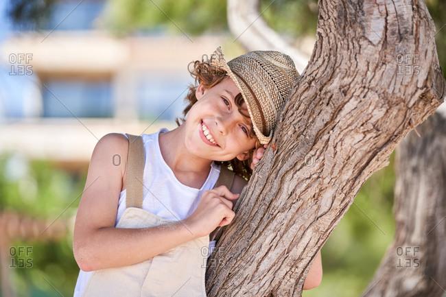 Joyful boy resting while leaning on the tree