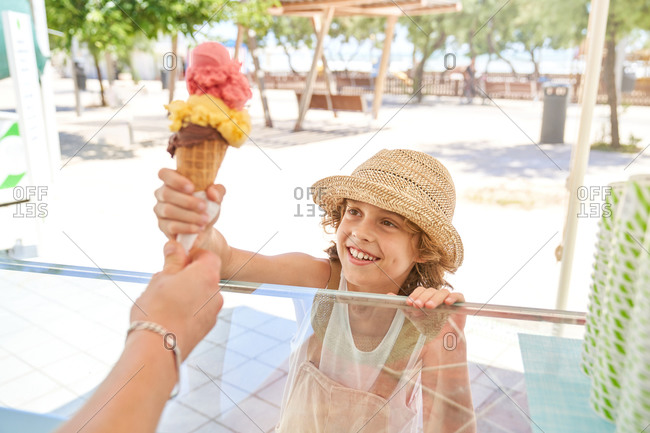 Crop ice cream shop assistant giving out ice cream in waffle cone for enthusiastic boy in straw hat