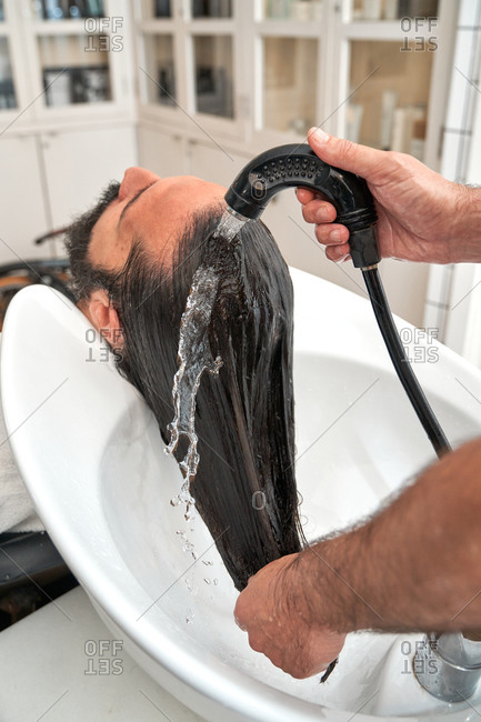 Back view of male barber washing head of bearded relaxing male customer in sink in barbershop