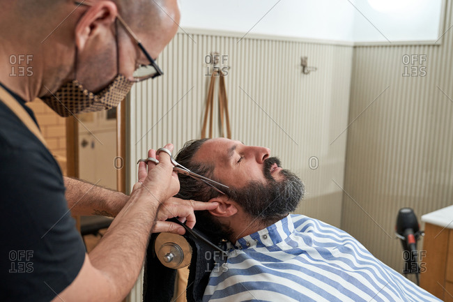 Barber in protective mask standing next to male consumer lying on comfortable hairdressing chair and cutting beard with scissors in modern salon