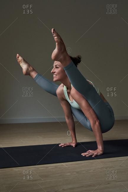 Side view of happy strong young female athlete in leggings balancing on arms while performing Firefly asana during yoga practice
