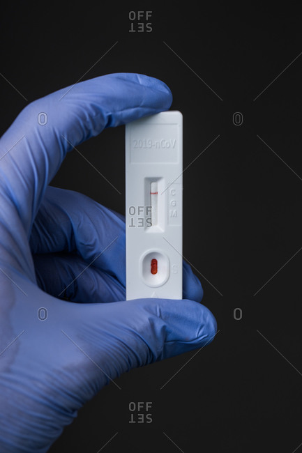 Unrecognizable doctor in medical gloves with results of rapid COVID 19 test on gray background in hospital