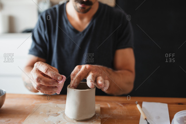 Unrecognizable ceramist using clay and creating cup while sitting at table and working in workshop