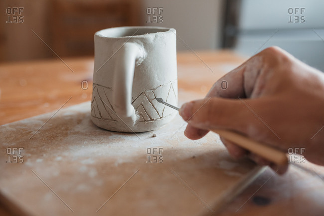 Unrecognizable ceramist with dirty hands using tool and creating pattern on clay cup in workshop