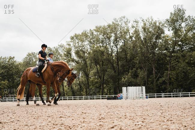 Ground level of female jockeys in uniform sitting in saddles and riding horses on sandy paddock during training