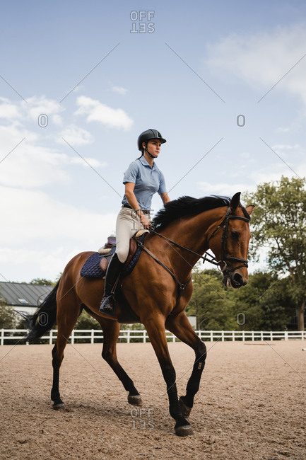 Female equestrian in uniform riding chestnut horse on sand arena during dressage on cloudy day