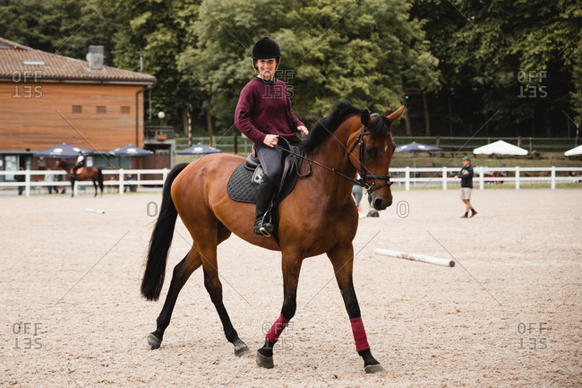 Smiley female equestrian in uniform riding chestnut horse on sand arena during dressage looking at camera