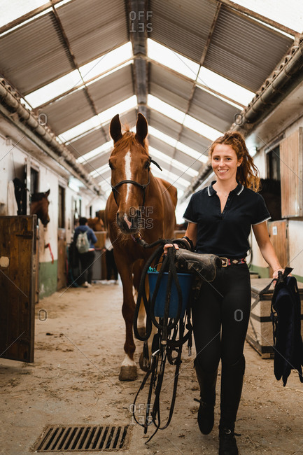 Smiling female equestrian with reins and bridle walking along stable with horse and looking at camera