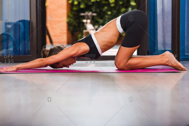 Side view of slender barefoot female in sportswear stretching back while practicing yoga on pink mat on floor in apartment