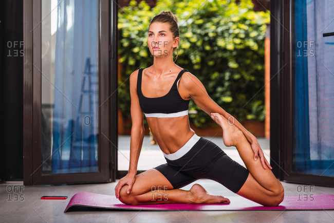 Confident slim female in sportswear sitting on mat and stretching legs before training