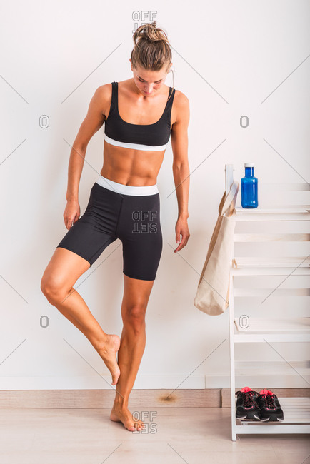Full body of slim female in activewear standing barefoot in gym and warming up legs before workout in modern fitness center