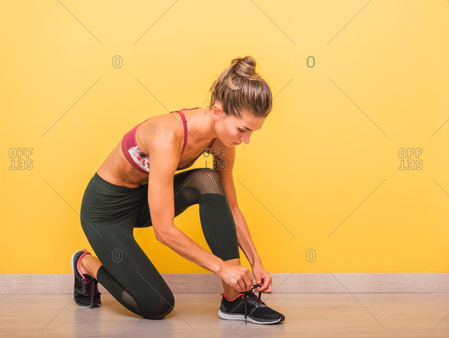 Side view of confident sportswoman in bra and leggings tying shoelaces on sneakers before training in modern gym