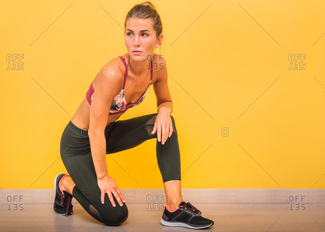 Weary sportswoman in activewear leaning on knee in vivid fitness center while resting during workout and looking away
