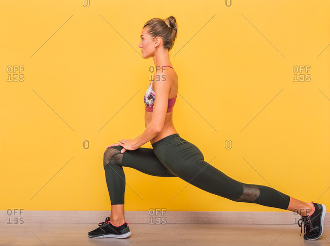 Side view of slim sportswoman in bra and leggings doing lunges while stretching legs and warming up before workout in vibrant fitness center