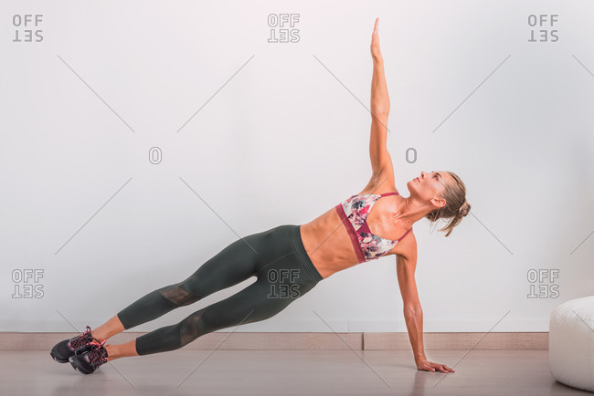 Fit female in sports clothes and sneakers standing in Side Plank pose with arm reached up while practicing yoga in flat near white wall and looking up