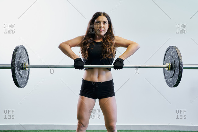 Confident female athlete in sportswear lifting heavy barbell while standing in gym during training and looking away