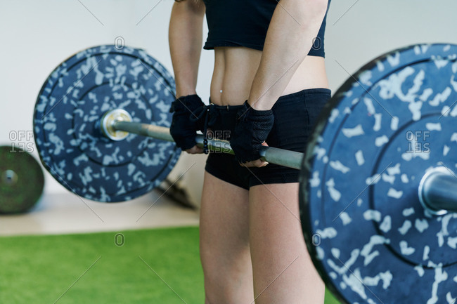 Unrecognizable crop sportswoman in activewear doing deadlift with heavy barbell during intense workout in modern fitness center