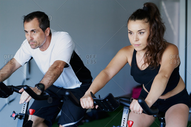 Muscular sportsman and sportswoman doing cardio exercises on cycling machines in gym