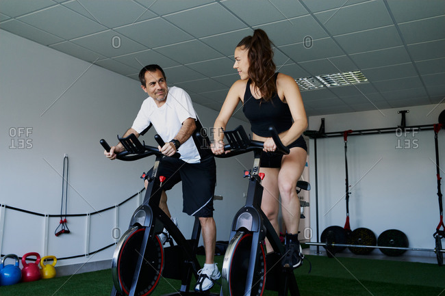 Muscular sportsman and sportswoman doing cardio exercises on cycling machines in gym while talking and looking at each other