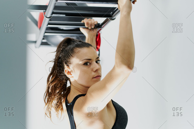 Side view of focused female athlete in sports bra doing pull ups in modern gym while looking at camera during active workout