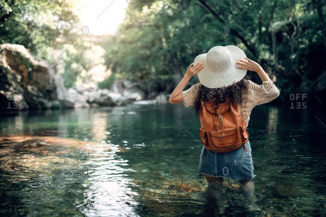 Back view of carefree female traveler in summer wear standing in water of river and touching sunhat while enjoying amazing scenery of forest