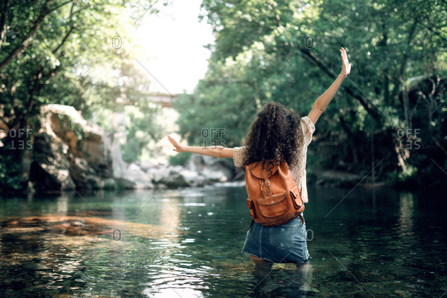 Cheerful female tourist in summer outfit standing in water of river and enjoying vacation with outstretched arms