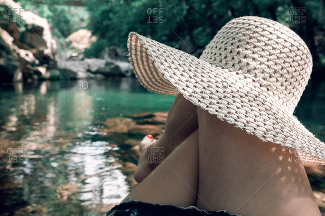Unrecognizable crop female traveler resting near calm lake with hat on knee while enjoying tranquil scenery during summer vacation