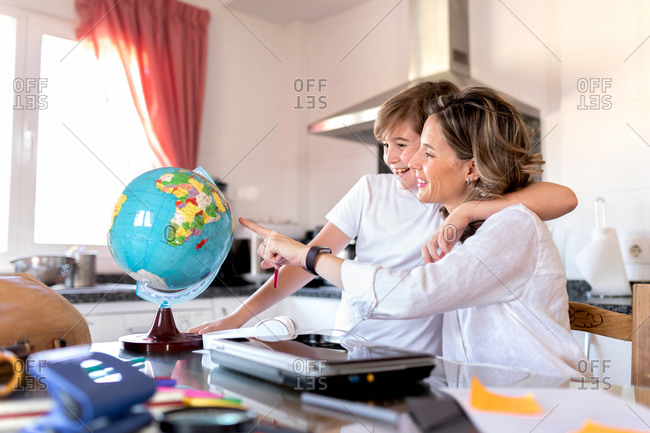 Positive boy cuddling gentle happy woman pointing with finger at colorful globe while sitting at table in kitchen and explaining geography lesson to son at home