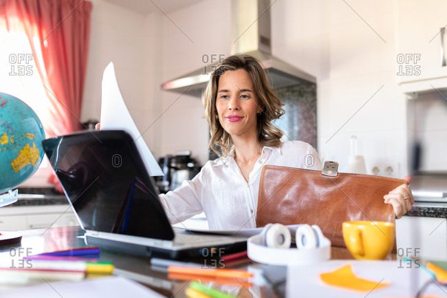 Cheerful adult female in headphones sitting at table with cup of hot drink in front of netbook during video chat near colorful stationery in light kitchen