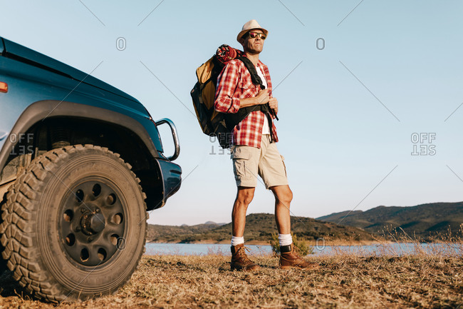 Male tourist in casual wear and hat enjoying picturesque nature while standing with backpack on faded grass near auto under serene sky in sunshine looking way