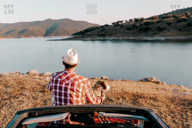 Back view of unrecognizable dreamy male traveler in hat sitting on auto near purebred dog with tongue out while admiring river and mountains on sunny day