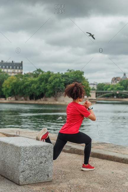 Back view of anonymous ethnic female athlete in active wear and smart watch stretching legs on embankment while exercising near pond in town in overcast weather
