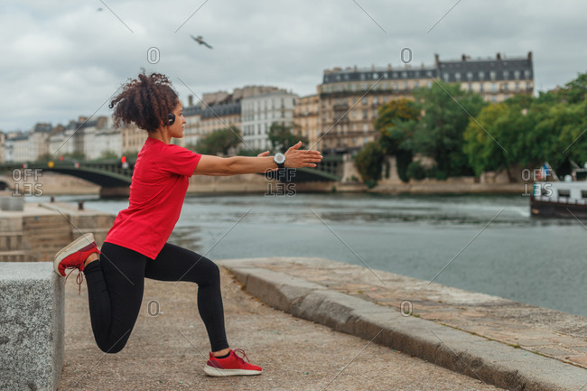 Side view of anonymous ethnic female athlete in active wear and smart watch stretching legs on embankment while exercising near pond in town in overcast weather