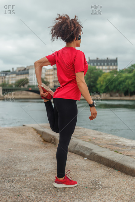 Back view of unrecognizable ethnic sportswoman in active wear and smart watch stretching legs while exercising on embankment near river and listening to music in headset under cloudy sky