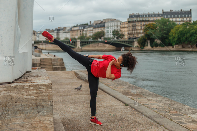 Side view of fit ethnic sportswoman in active wear and smart watch doing roundhouse kick while training on embankment near pond in town behind buildings in overcast weather