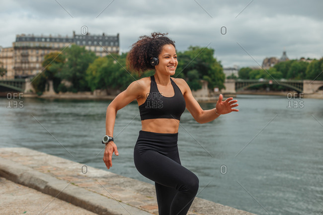 Young happy ethnic sportswoman in active wear and smart watch listening to music in headphones during workout near pond in town and looking away