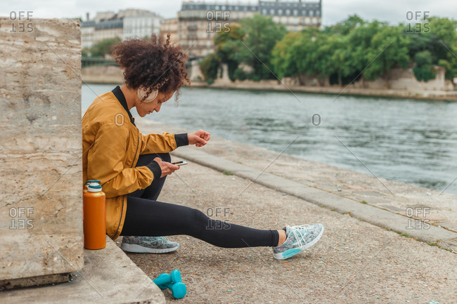 Side view of ethnic female athlete in active wear and headphones chatting on cellphone after training while sitting on embankment with dumbbells near city river
