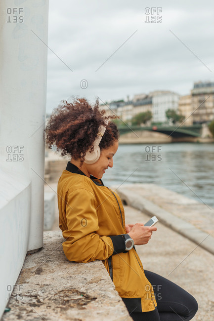 Side view of ethnic female athlete in active wear and headphones chatting on cellphone after training while standing on embankment with dumbbells near city river