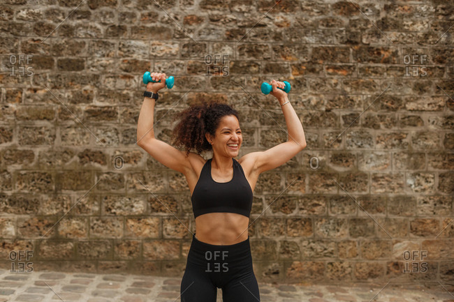 Woman athlete in sports clothes training shoulders using dumbbells near rough wall