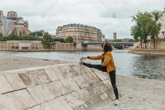 Side view of fit ethnic female athlete listening to music in wireless headphones while stretching leg during workout on embankment near pond and building in town under cloudy sky