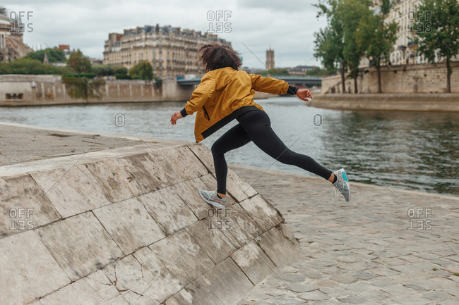 Side view of faceless ethnic female athlete in sports clothes and jacket warming up while climbing stone platform on pavement near pond in town behind buildings