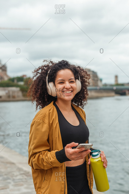 Woman athlete in active wear and headphones holding cellphone after training while standing on embankment near city river