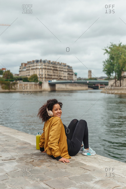 Side view of cheerful ethnic slender female athlete listening to music in headphones while resting on embankment after training and looking back at camera